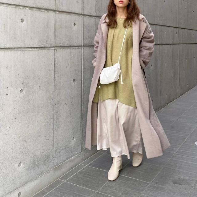 ライトグリーンのニットにコートを着用した女性