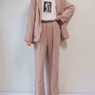 くすみピンクのジャケットとパンツセットアップを着た女性