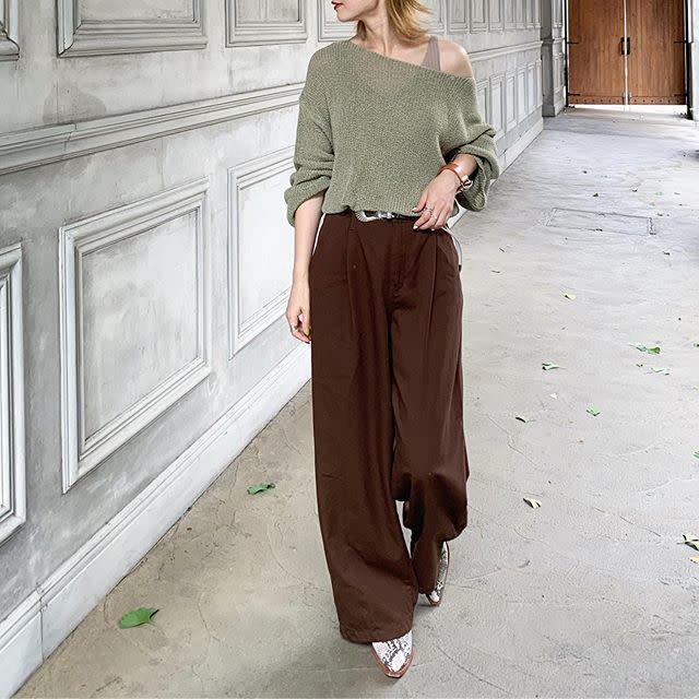 ピスタチオカラーのニットにブラウンのワイドパンツを着用した女性