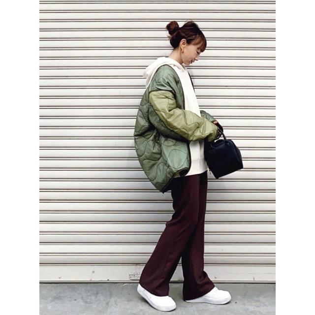 カーキのキルティングコートにパーカーとパンツを着用した女性