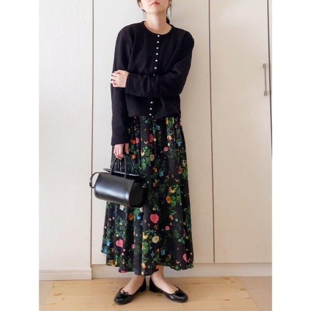 黒のトップスと花柄スカートを着用した女性