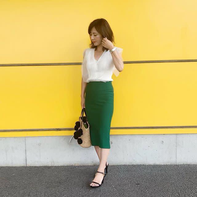 エメラルドグリーンのスカートに白トップスを着た女性