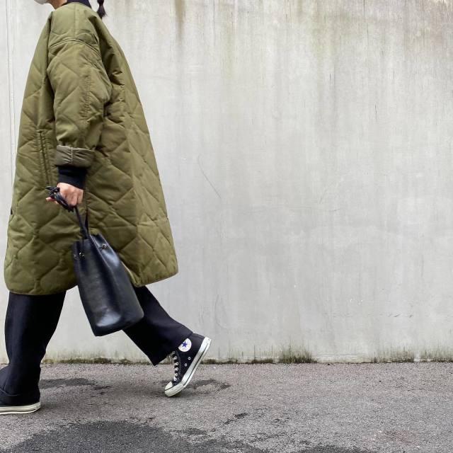 カーキのキルティングコートにコンバースのスニーカーを履いた女性
