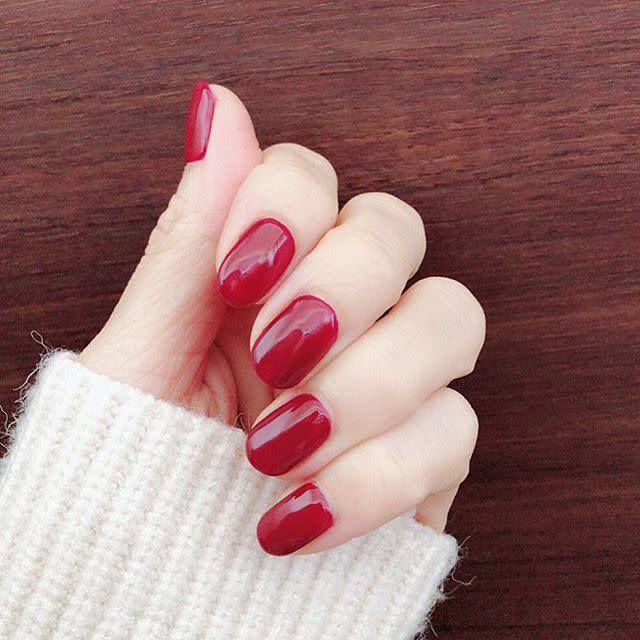 ホワイトニットの袖からのぞく赤いネイルの女性の手