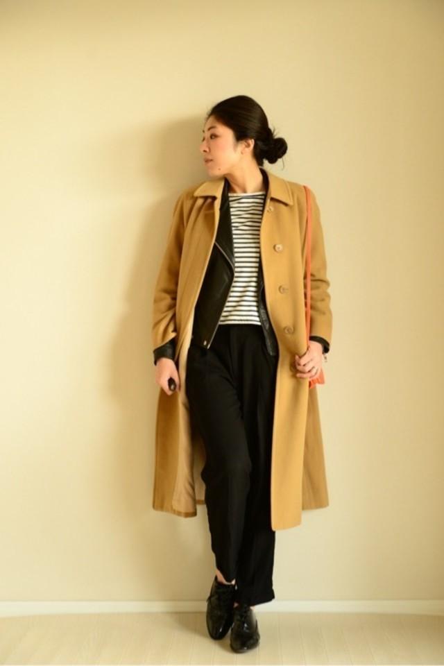 ライダースジャケットにキャメルのチェスターコートを重ね着した女性