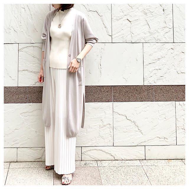 ライトグレーのロングカーディガンとワイドパンツを着用した女性