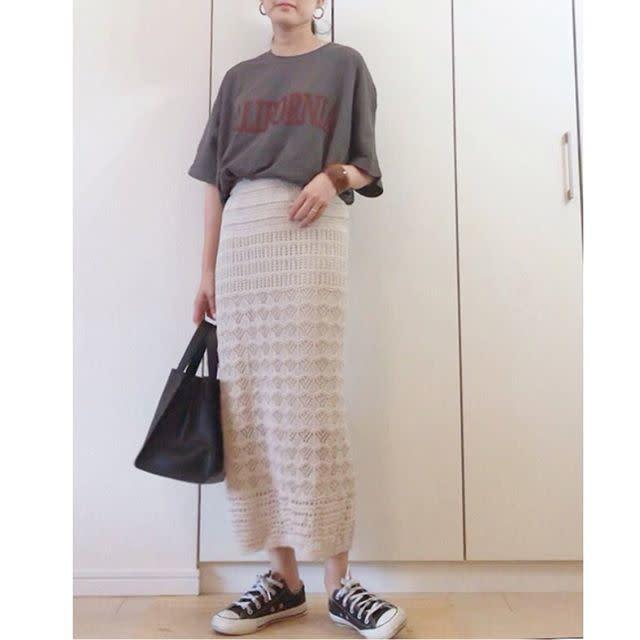 ロゴTシャツとニットスカートを履いてる女性