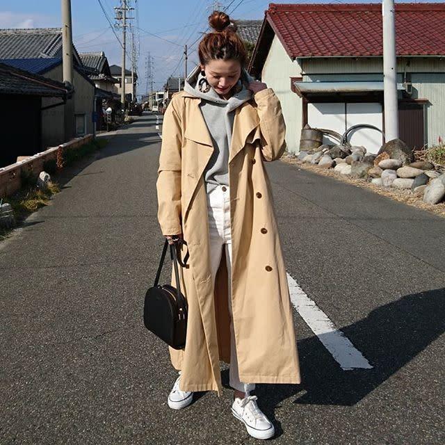 ベージュトレンチコートにグレーのフード付きパーカーを着た女性