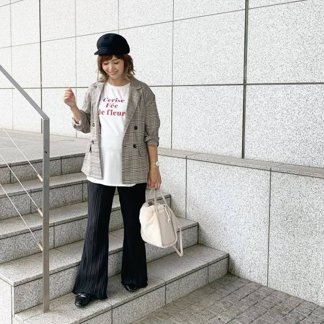 白のロゴTシャツにベルボトムを履いた女性