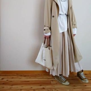 トレンチコートにベージュのロングプリーツスカートを着た女性