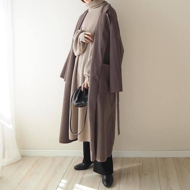 ブラウンのコートとロングニットとワイドパンツを着用した女性