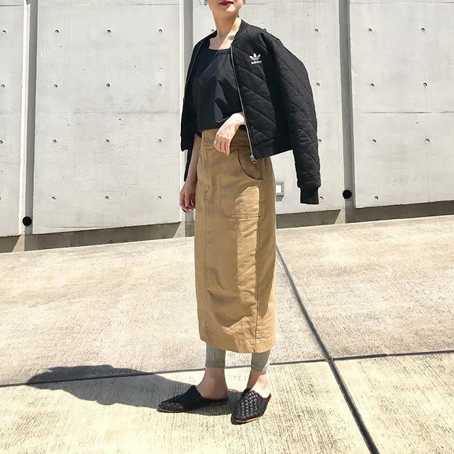 スポーツウェア調の黒シャツとチノスカートを合わせたレディースコーデ