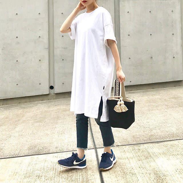 白のTシャツワンピースにカットオフデニムパンツを合わせたコーデ