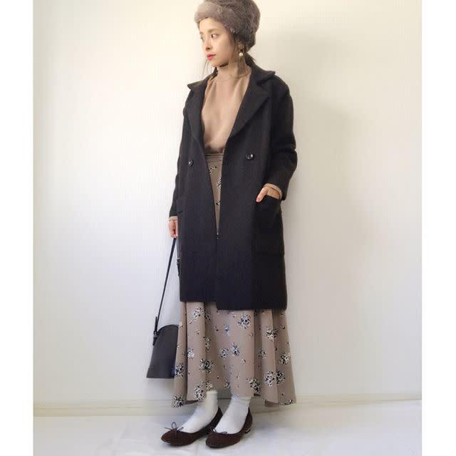 黒のロングPコートを着た女性