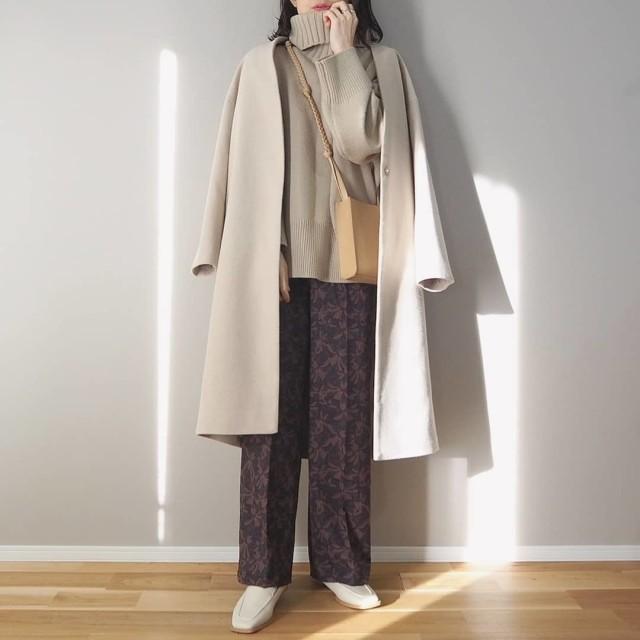 ベージュのノーカラーコートを着た女性