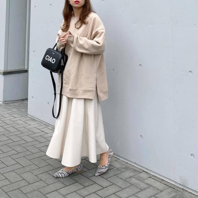 ベージュのスウェットと白のスカートを着用した女性