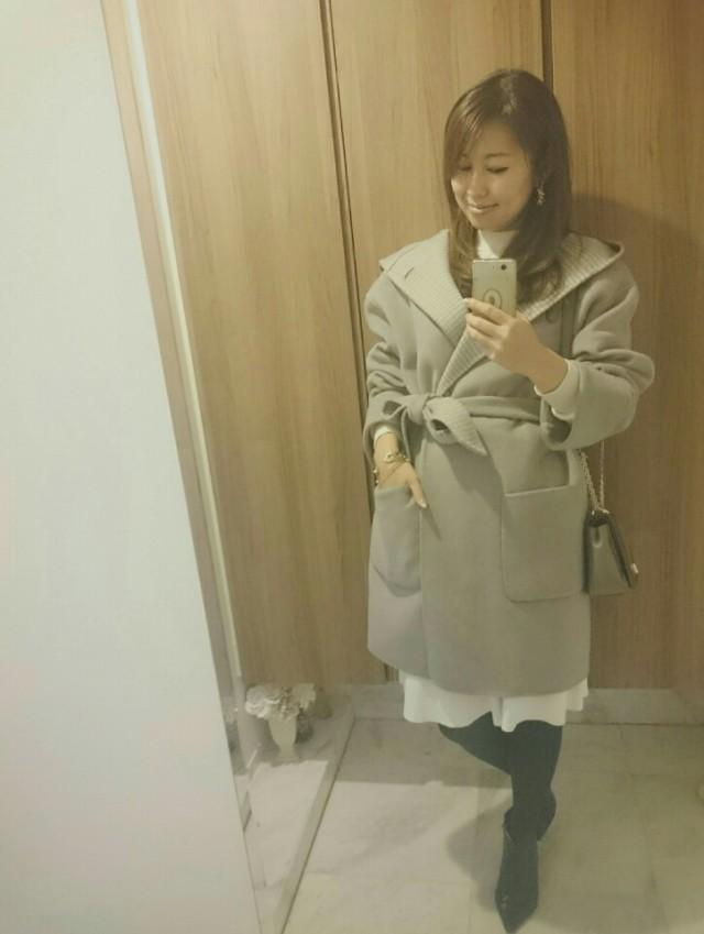 グレーのロングコートと白のスカートのコーデ