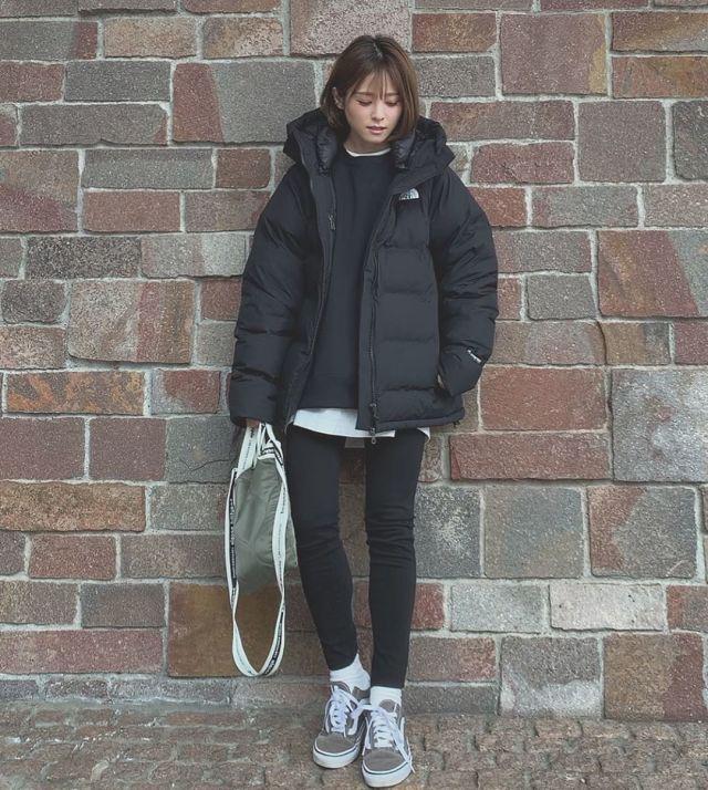 黒のダウンコートとパンツでオールブラックコーデの女性