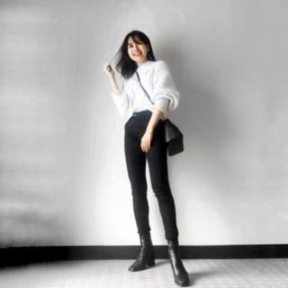 白ニットと濃紺スキニーとブーツを合わせた女性