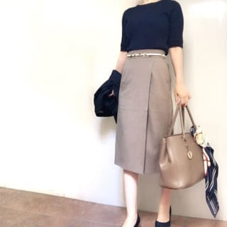 黒のトップスに合わせてべージュスカートのコーデにフルラバッグを持つ女性