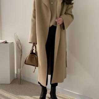 ベージュのコートとタートルニットを着用した女性
