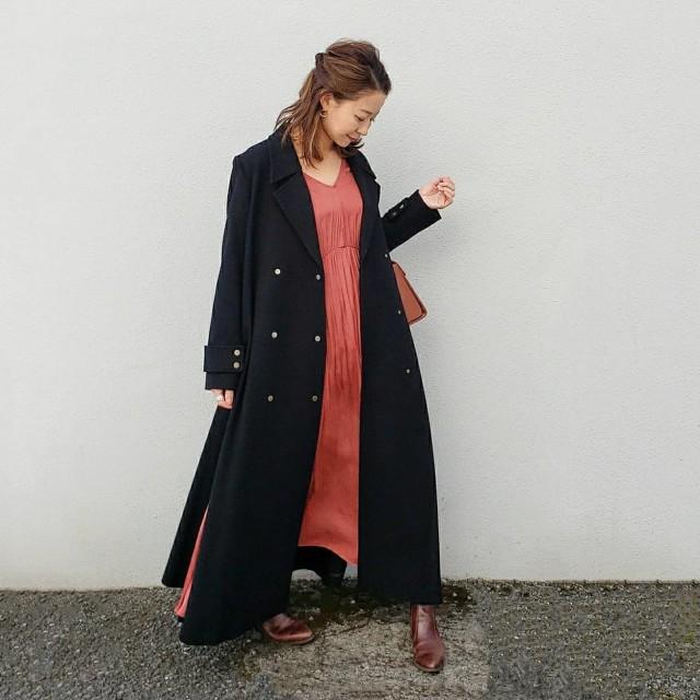 黒のチェスターコートとピンクのワンピースのコーデ