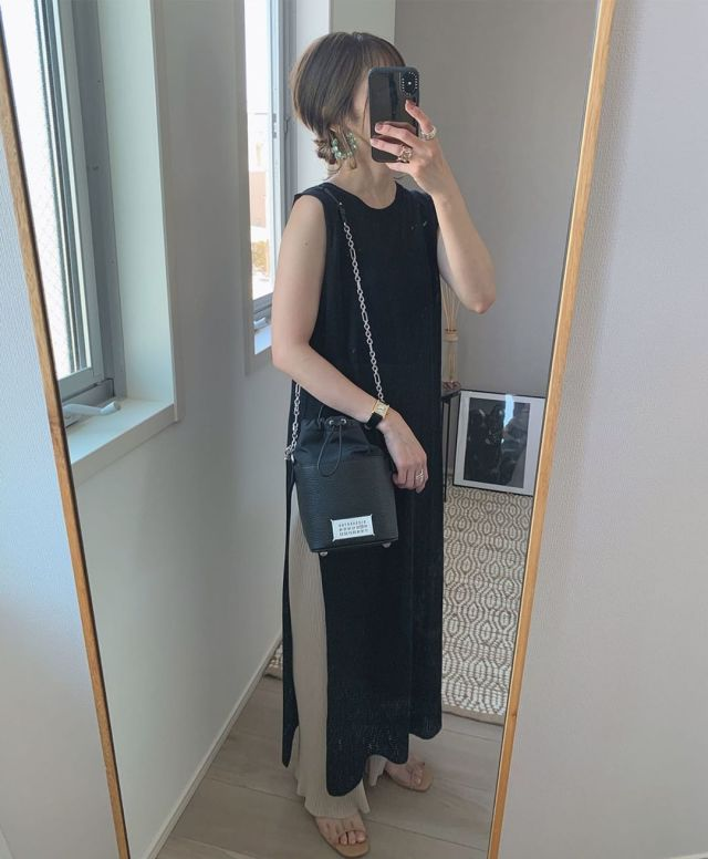 黒のワンピースとリブパンツを着用した女性
