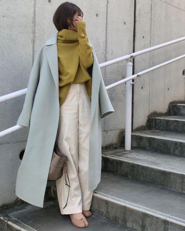 ブルーのロングコートとニットとワイドパンツを着用した女性
