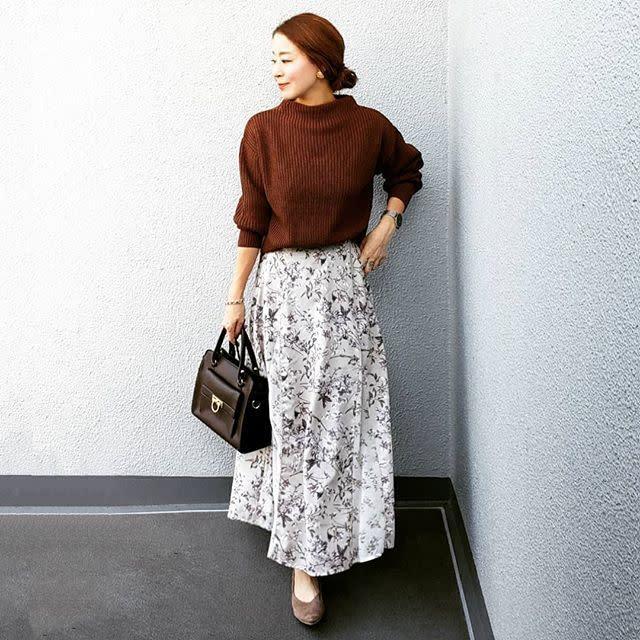 ブラウンのニットとスカートを着用した女性