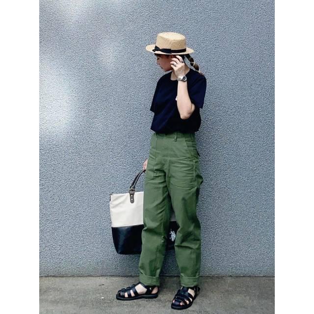 黒のトップスとカーキのパンツを着用した女性