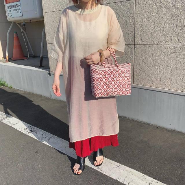 シアーワンピースと赤のスカートを着用した女性