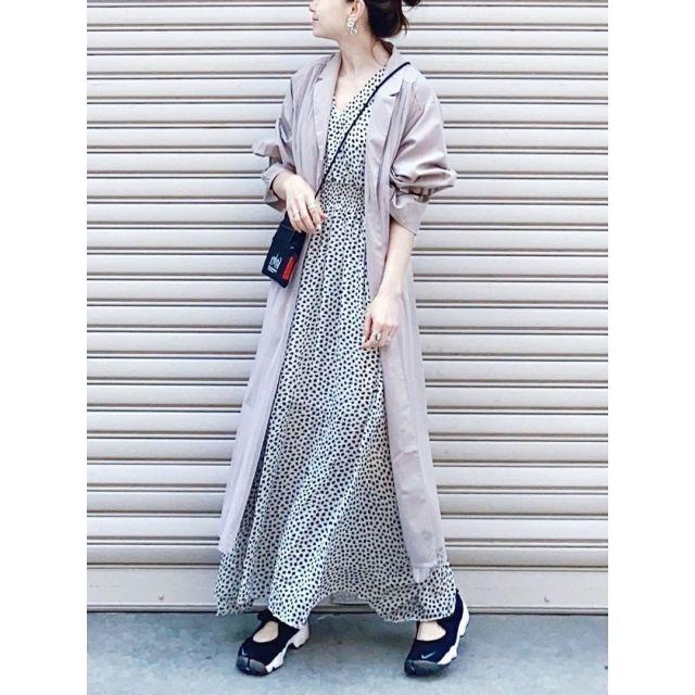 トレンチコートとダルメシアン柄のワンピースを着用した女性