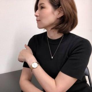 腕時計とネックレスをつけている女性