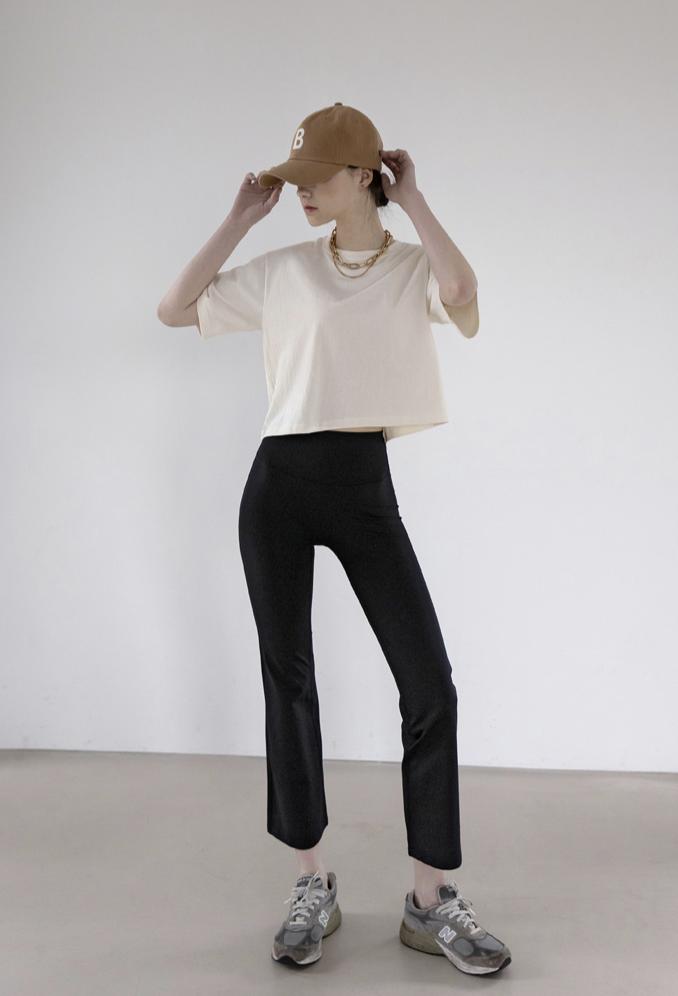 ショート丈のTシャツとスキニーパンツを着用した女性