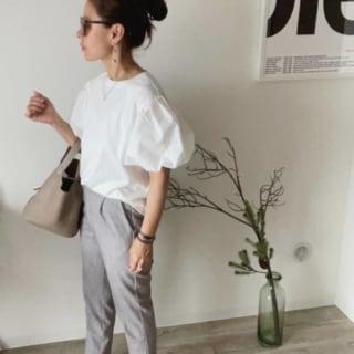 白のバルーンTシャツにシルバーのドロップイヤリングを合わせた女性