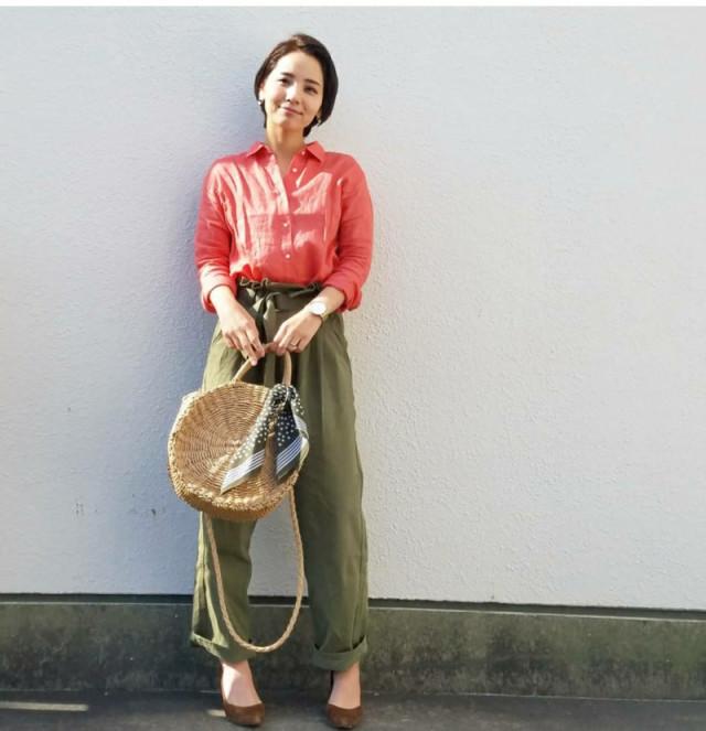 赤リネンシャツとカーキパンツの女性