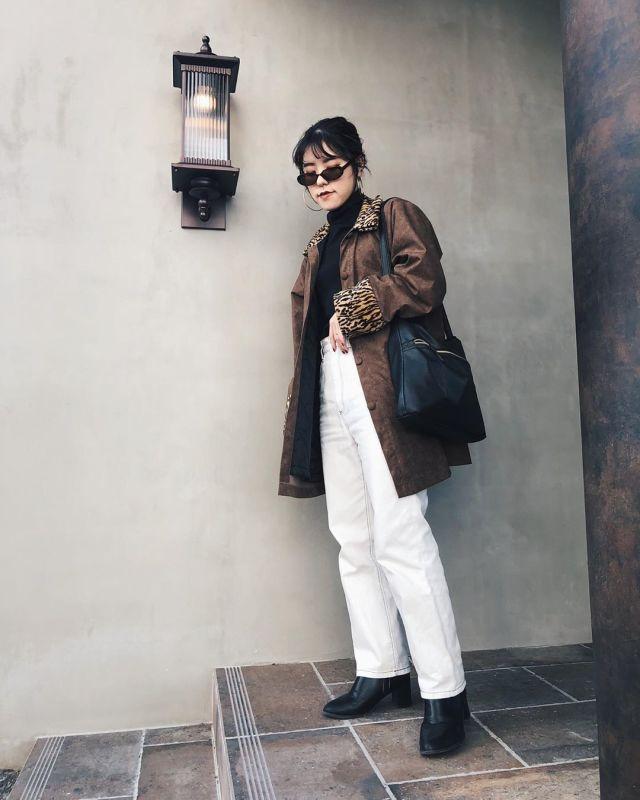 ブラウンのコートと白パンツを着用した女性