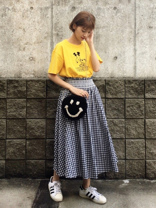黄色プリントTシャツとギンガムチェックスカートとスニーカー女子