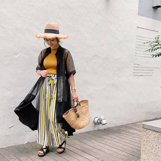 黄インナーにストライプパンツに黒のシアーシャツとむ麦わらの女子