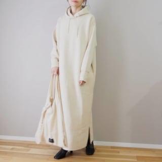 白のフード付きスウェットワンピースを着用した女性