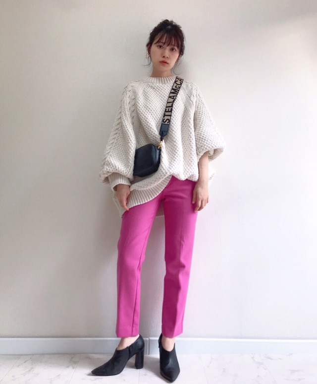 白ニットとピンクのパンツを着用した女性