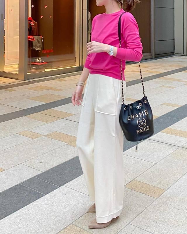 ピンクのニットと白パンツを着用した女性
