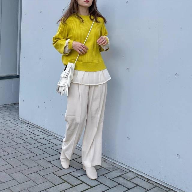 黄色のニットと白パンツを着用した女性