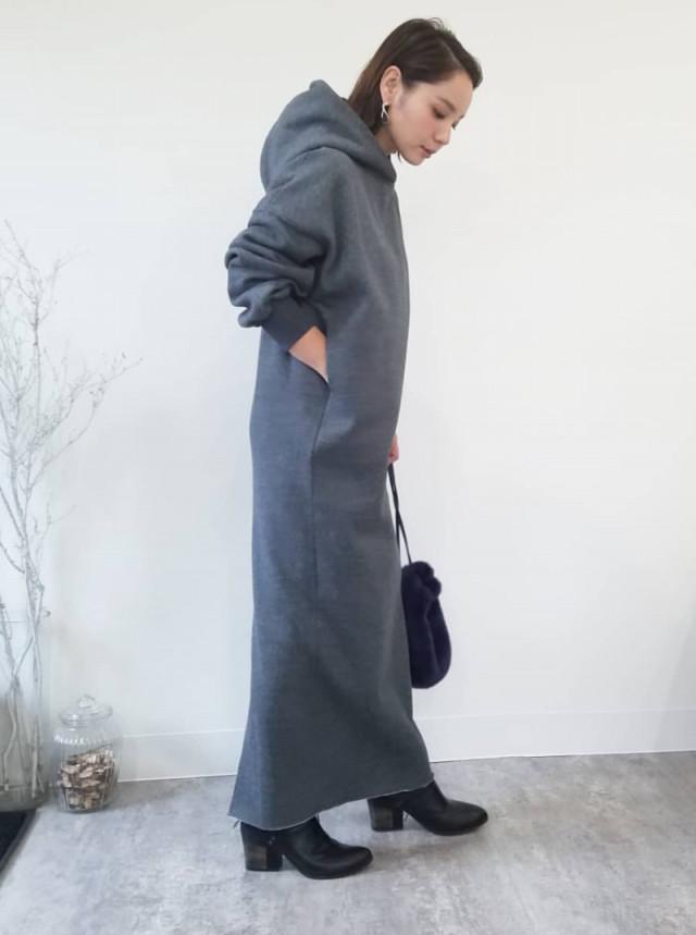 チャコールグレーのフード付きスウェットワンピを着用した女性