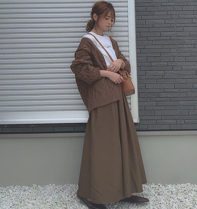 ニットカーディガンとTシャツとスカートを着用した女性