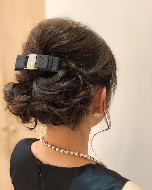 結婚式用のアップヘアにアレンジしている女性
