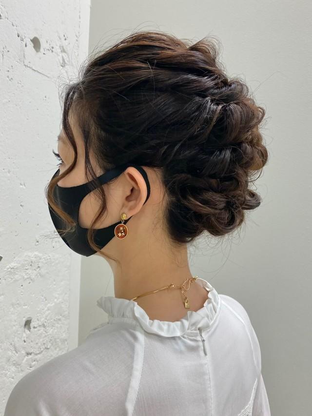 結婚式用のヘアアレンジで髪をまとめ髪にしている女性