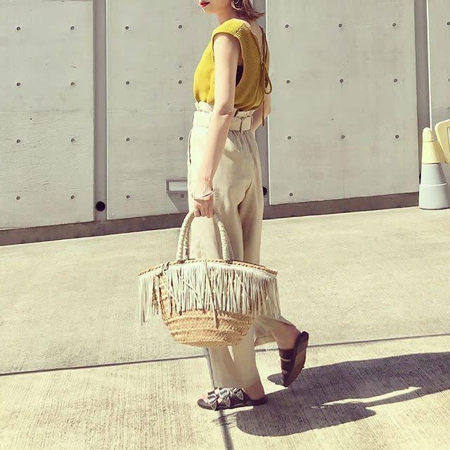 イエローのノースリーブとベージュのチノパンを着用した女性