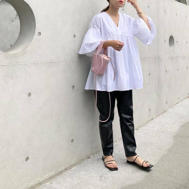 バルーン袖の白トップスに黒パンツを合わせたコーデ。