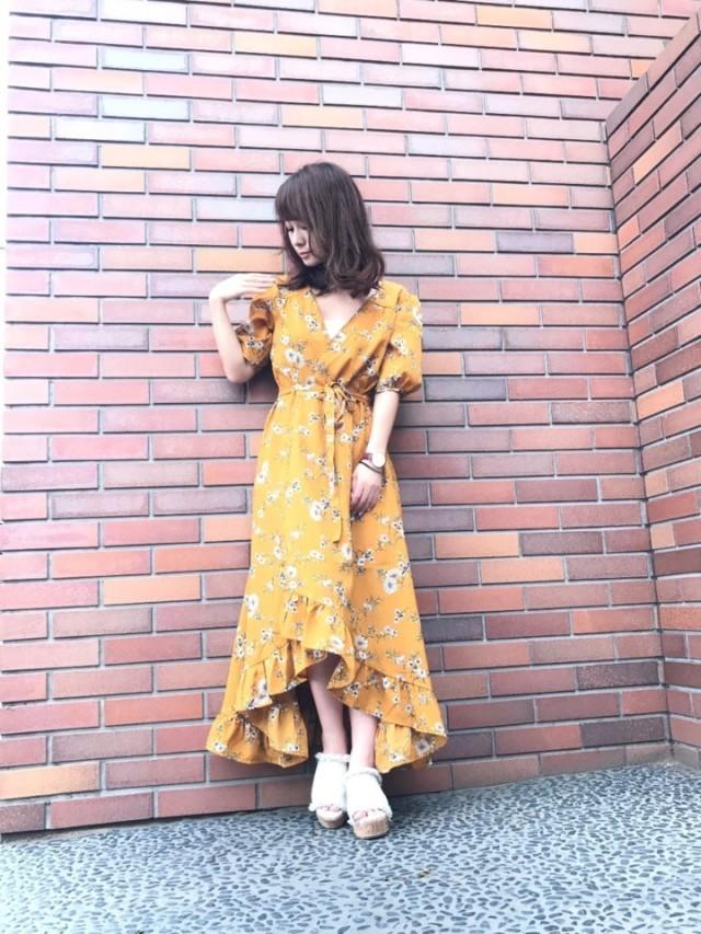 黄色の花柄カシュクールワンピの女性